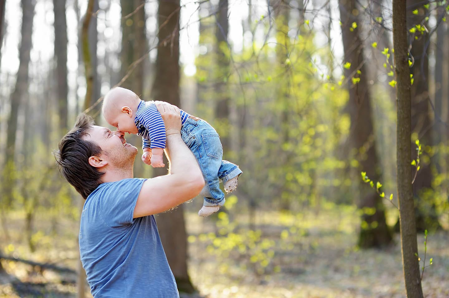 man holding up baby