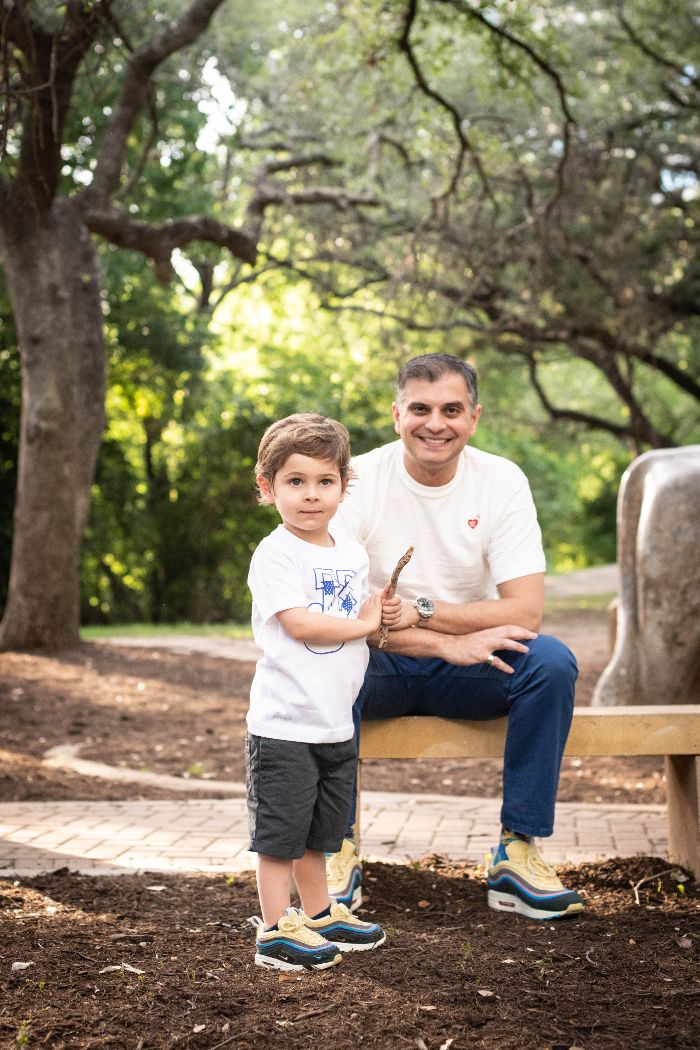 dr. sam and his son sitting on bench in forrest