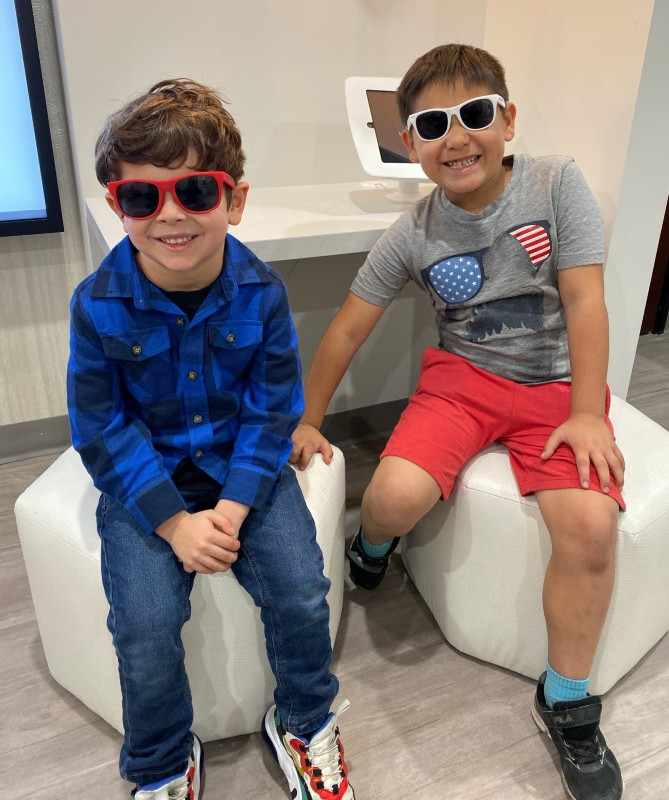 two boys smiling with sunglasses
