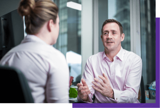 A man and a woman discuss in a business setting