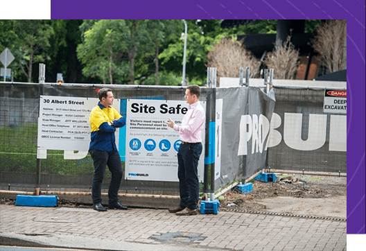 two men stand outside of construction site