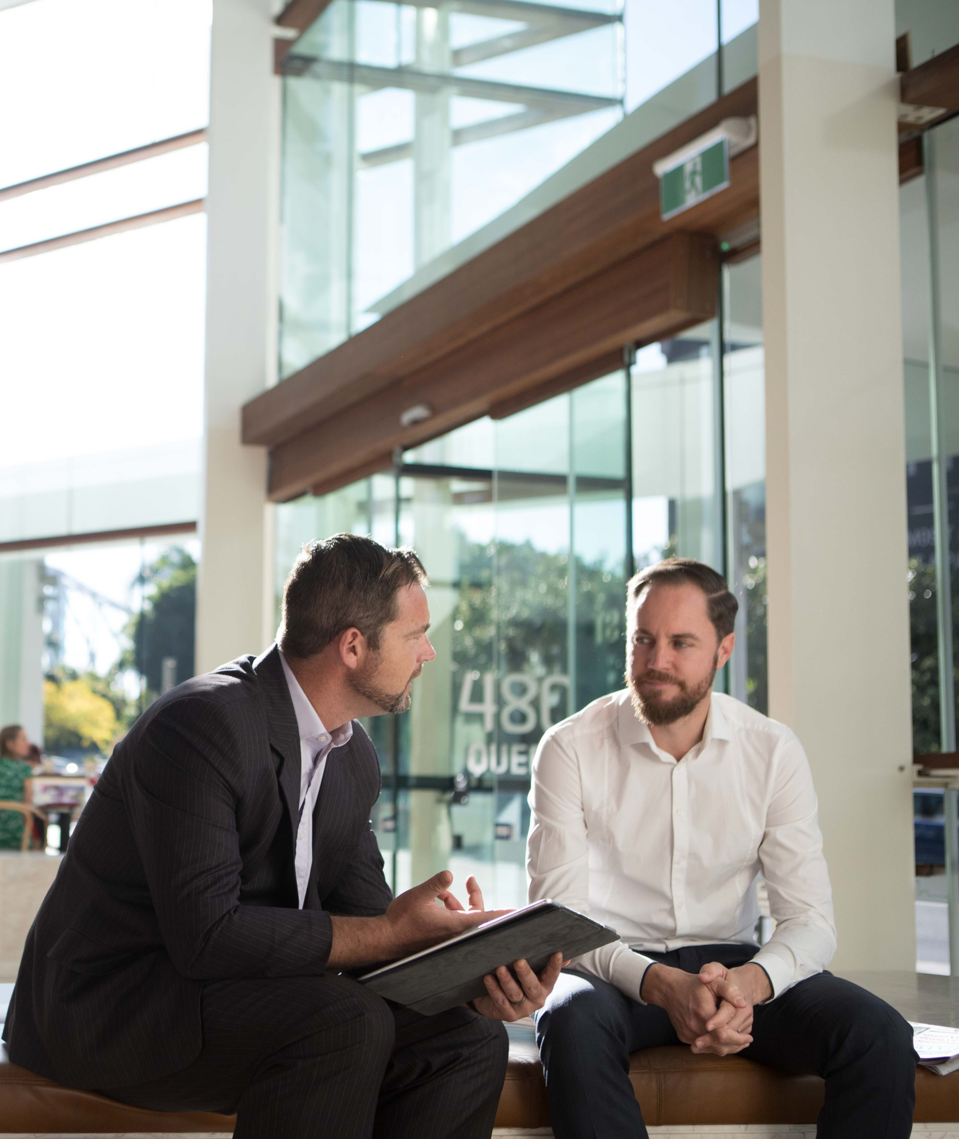 Two men discuss matters in a foyer