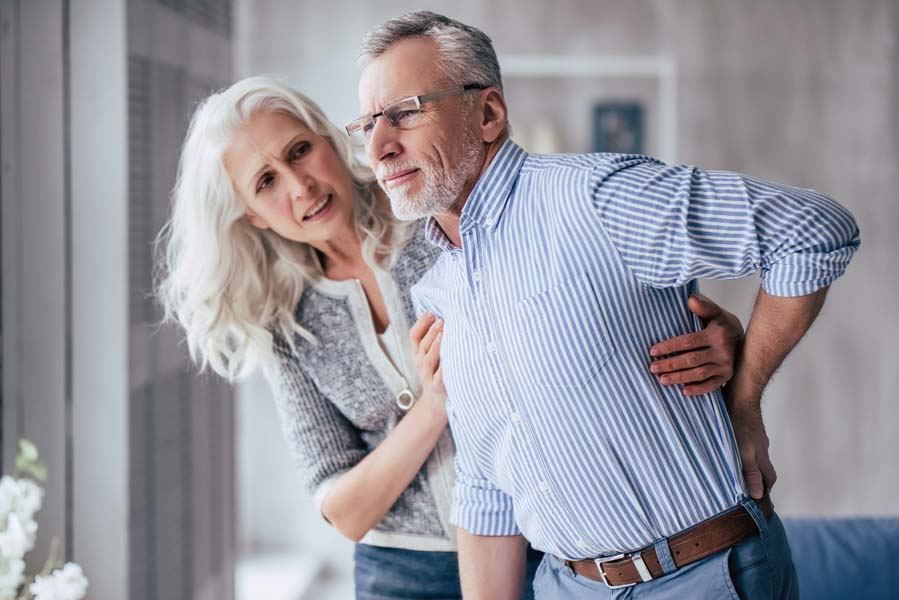man with back pain being helped by woman