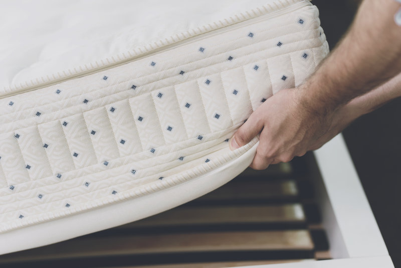 lifting a white mattress