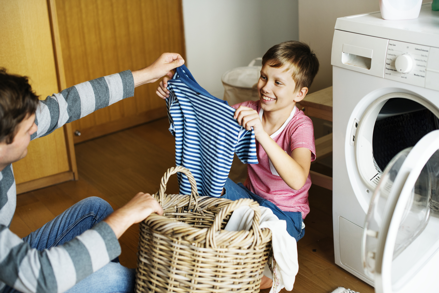 kid helping dad with laundry