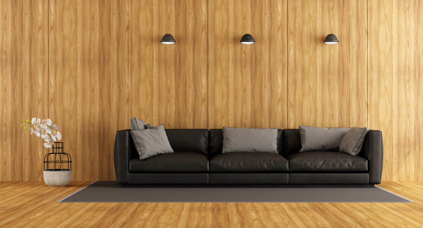 black sofa with gray pillows on wooden wall and flooring