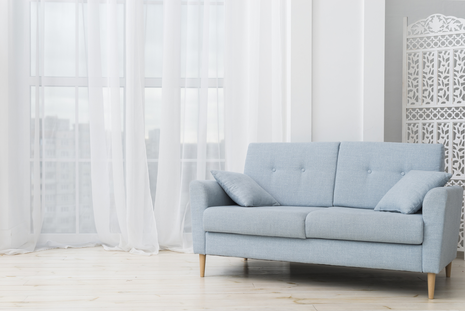 teal fabric sofa with white curtains background