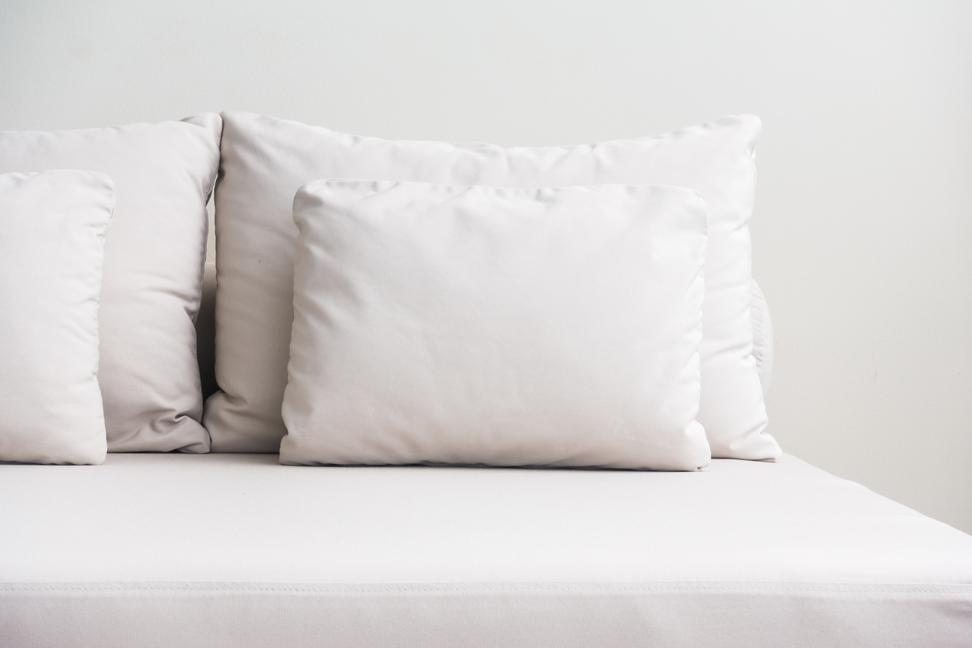 white latex pillows against each other on white sofa