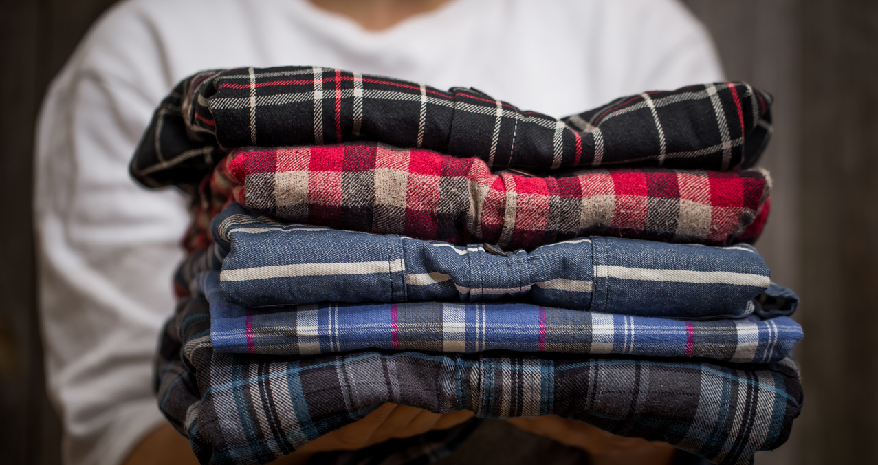 a man holding a stack of plaid clothes