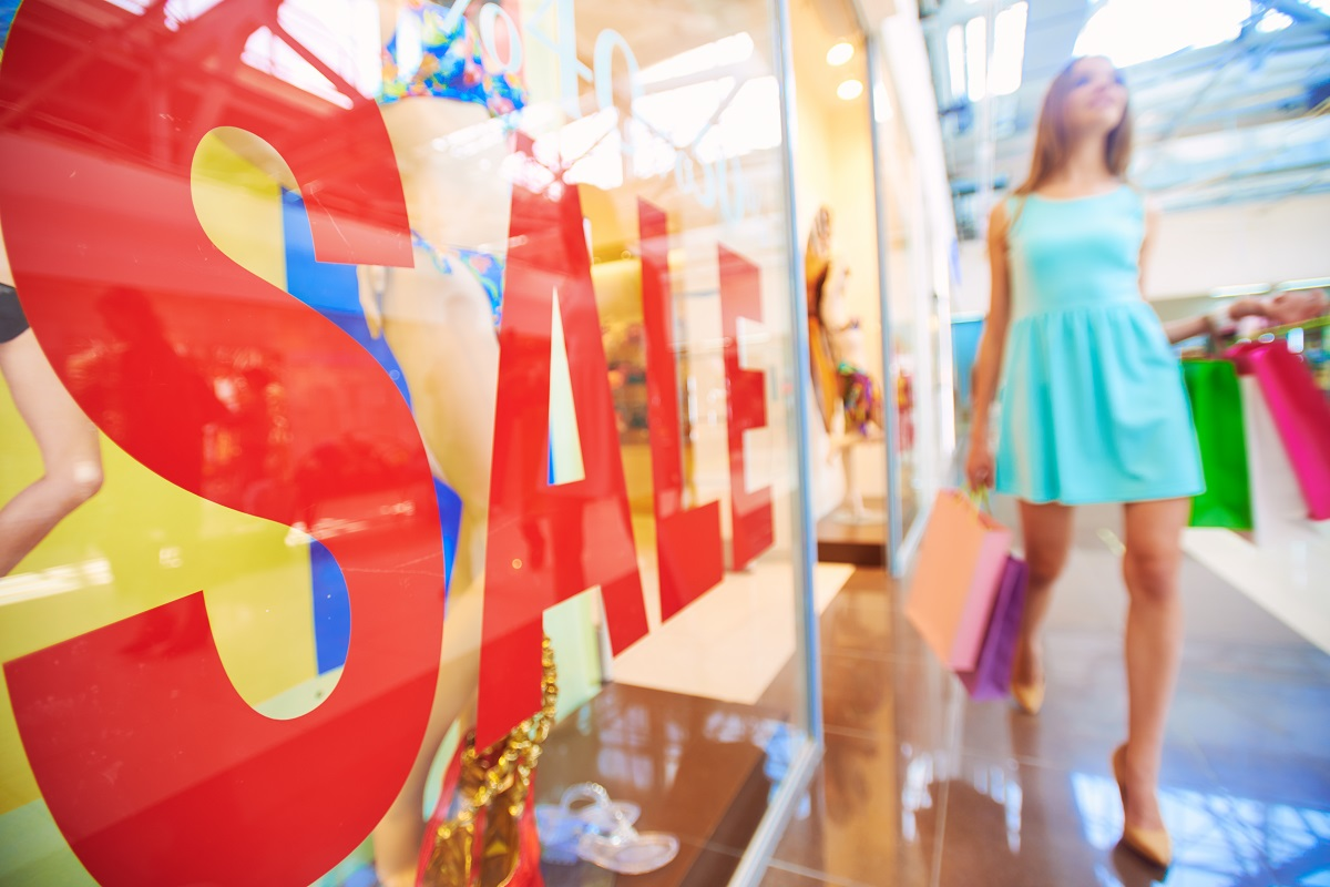 woman walking by a sale sign