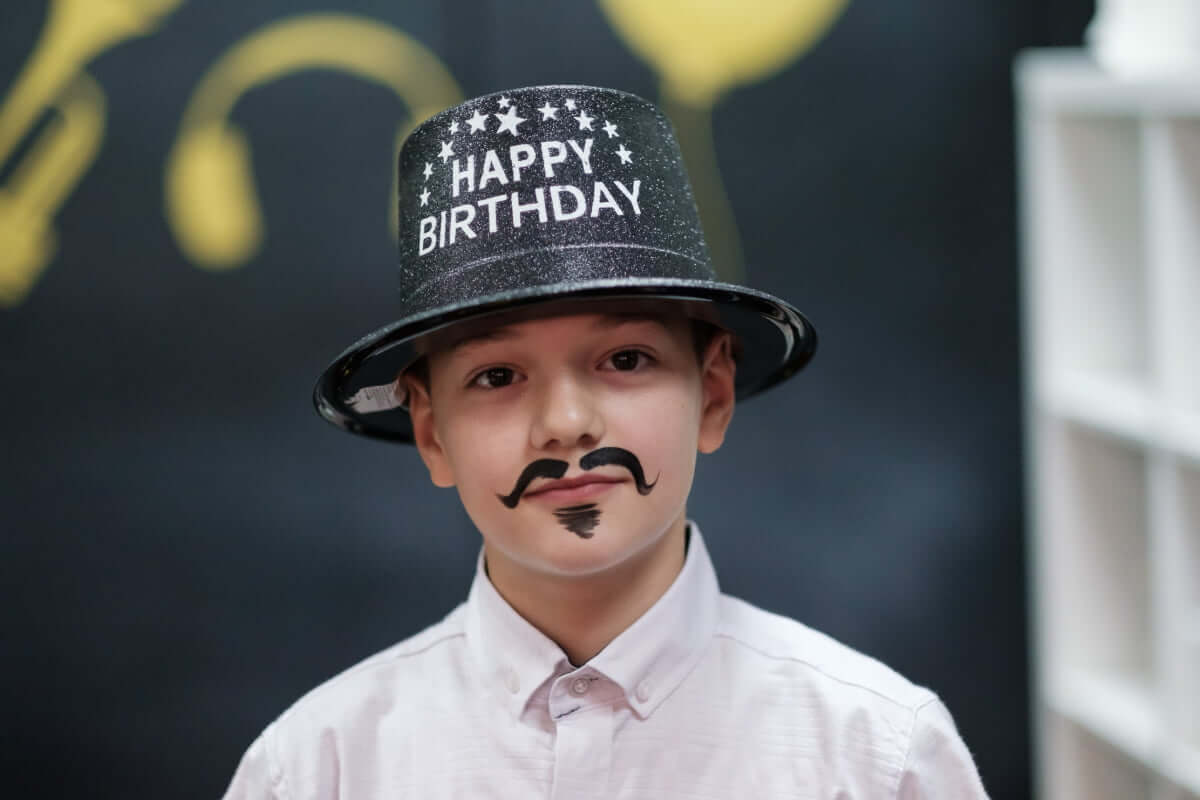 A kid in a happy birthday hat