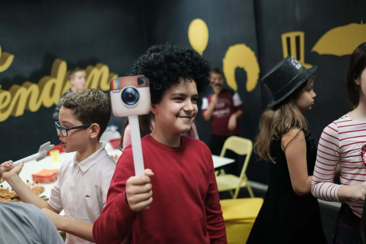 Kid with afro posing with an Instagram stick