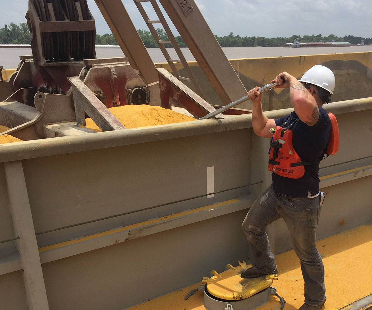 man in a hard hat taking a sample of grains on boat