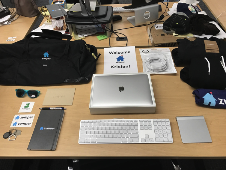 First Day Onboarding Ideas for New Hires: Zumper prepares a new hire's desk with company swag.