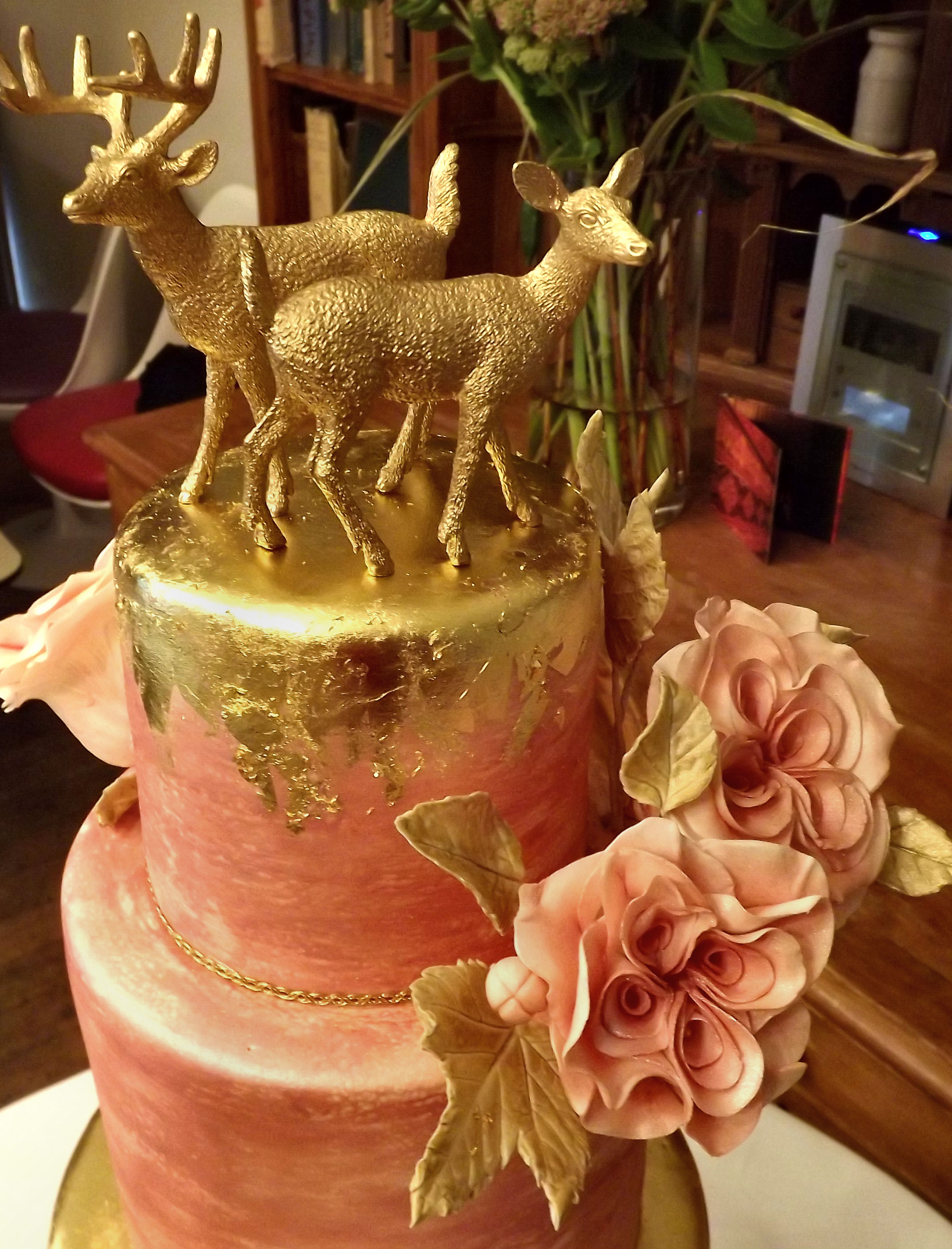 pink and gold wedding cake with stags