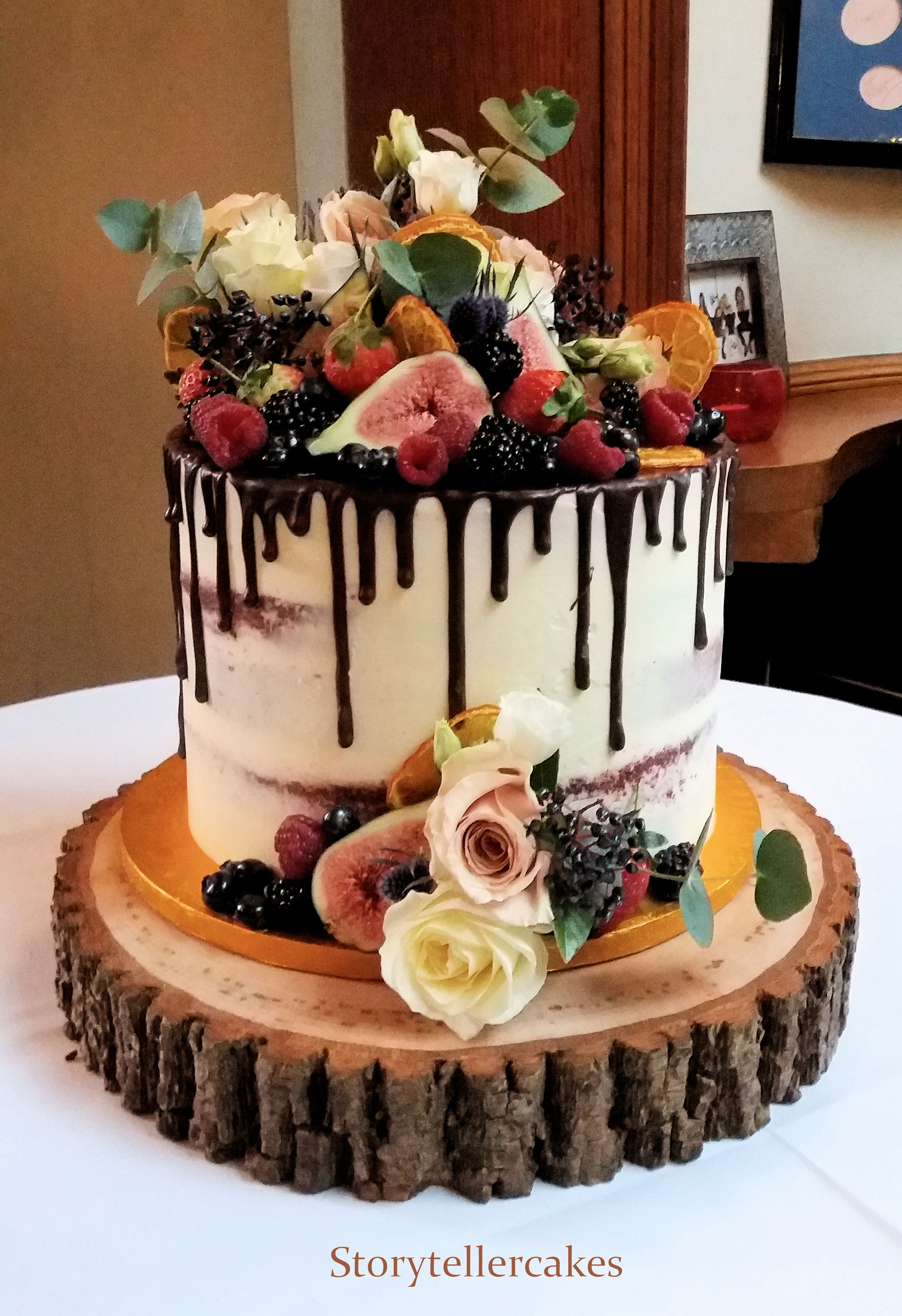 chocolate drip fresh fruit and flowers wedding cake