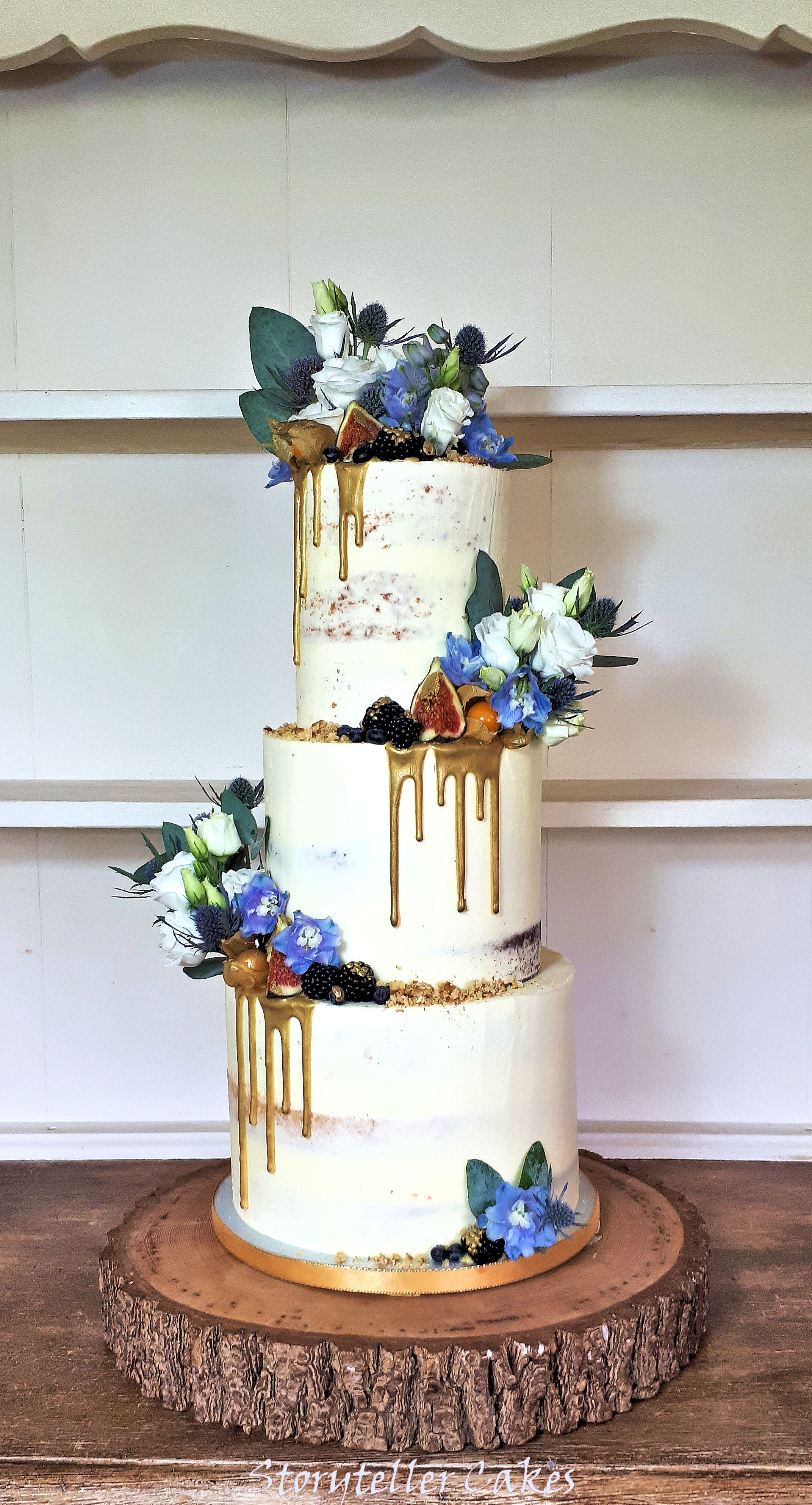 semi naked cake with blue flowers and fresh fruits