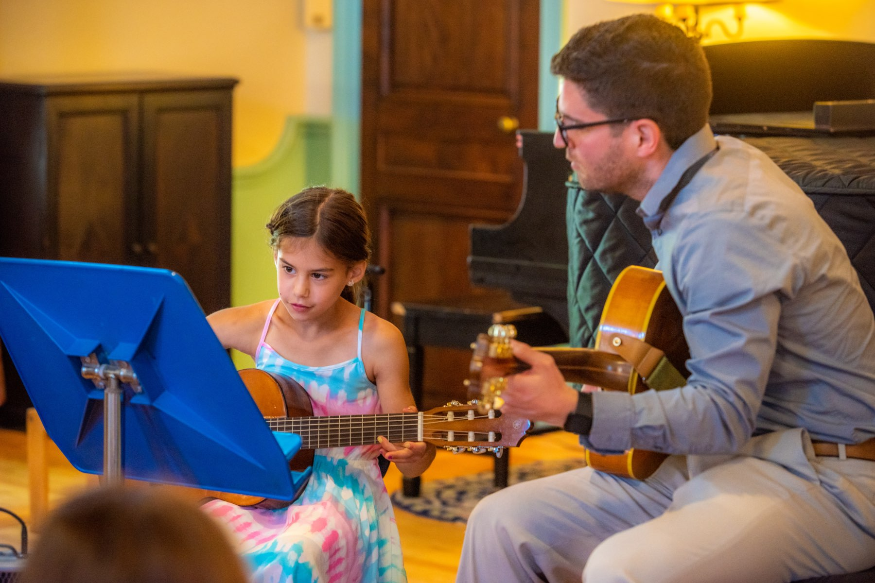 young student at recital playing guitar next to instructor.