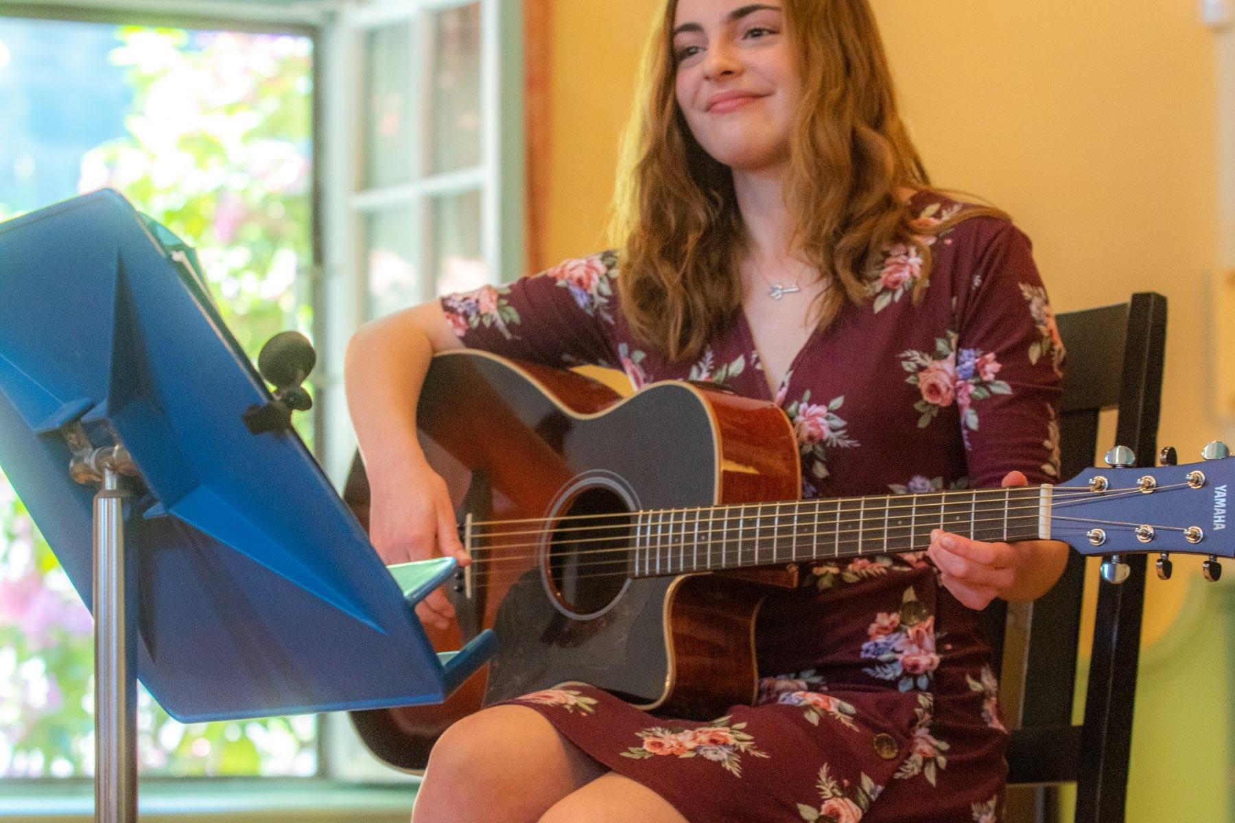 Student playing guitar, close up image.
