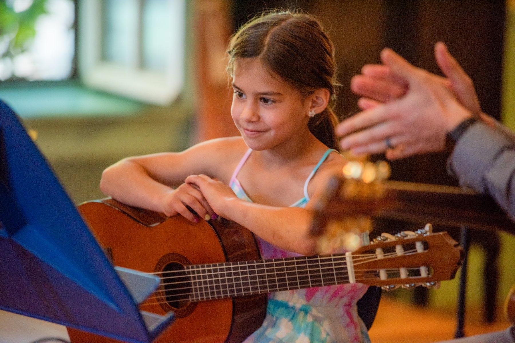 A student plays guitar, close up image.