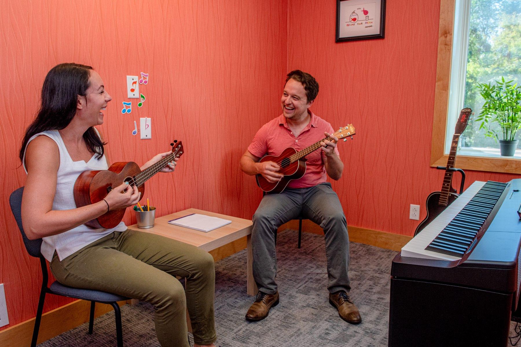 Instructor and student playing ukulele.