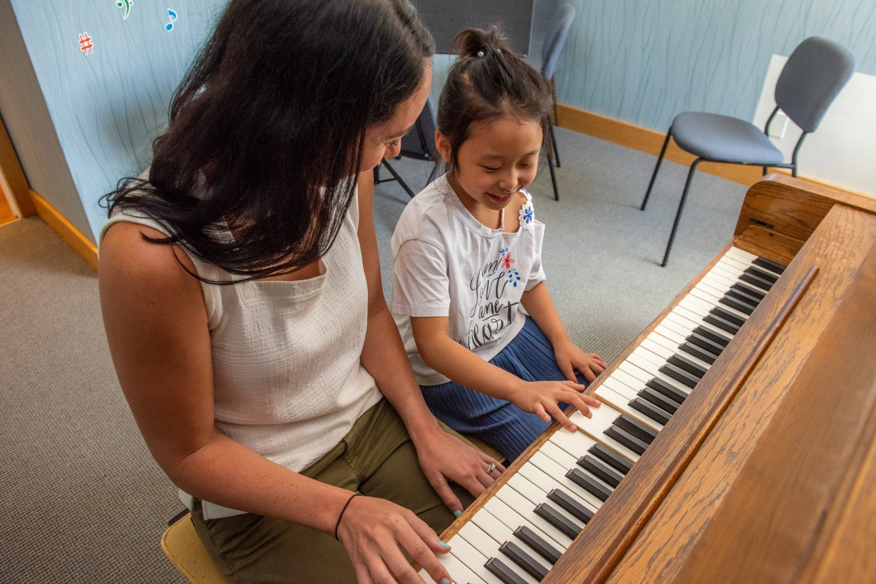 Student and teacher enjoy piano lesson.
