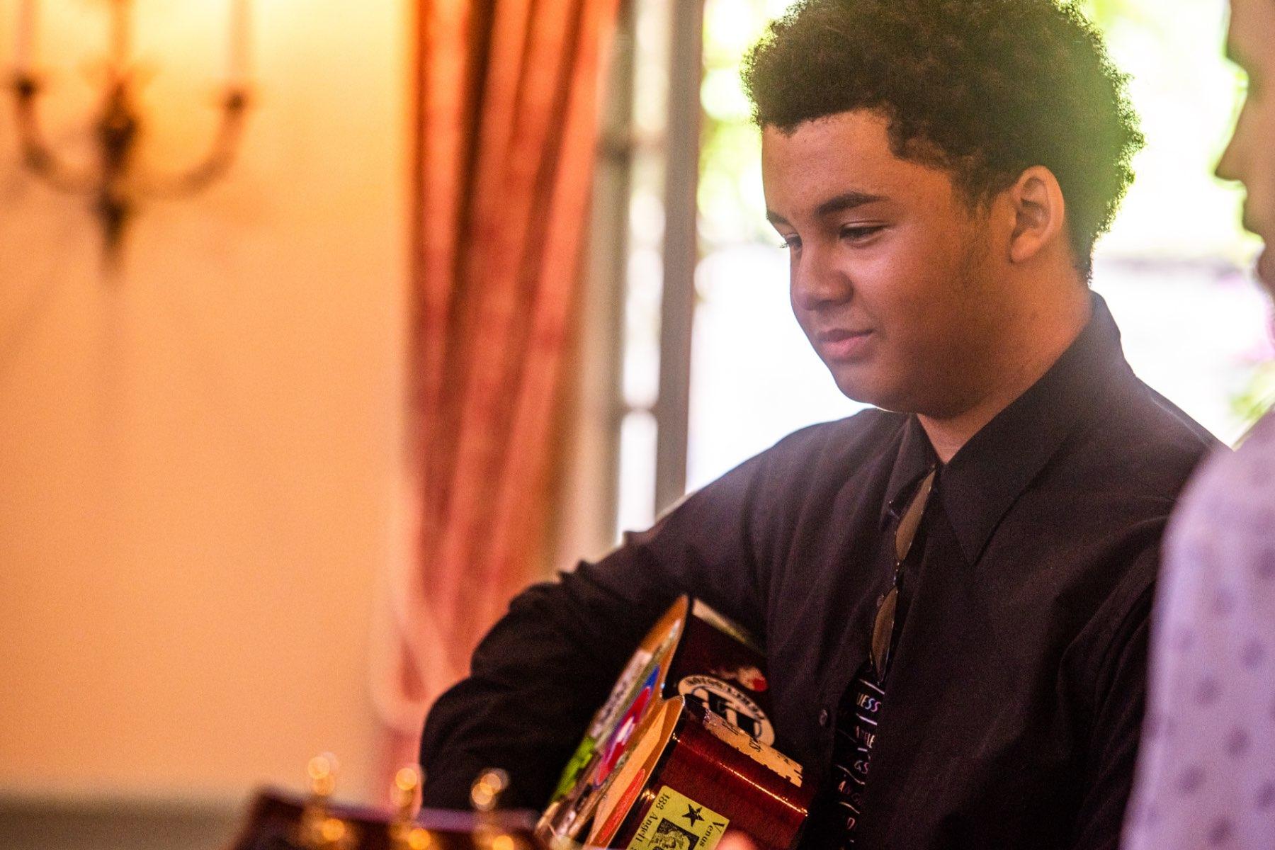 close up student playing guitar at recital