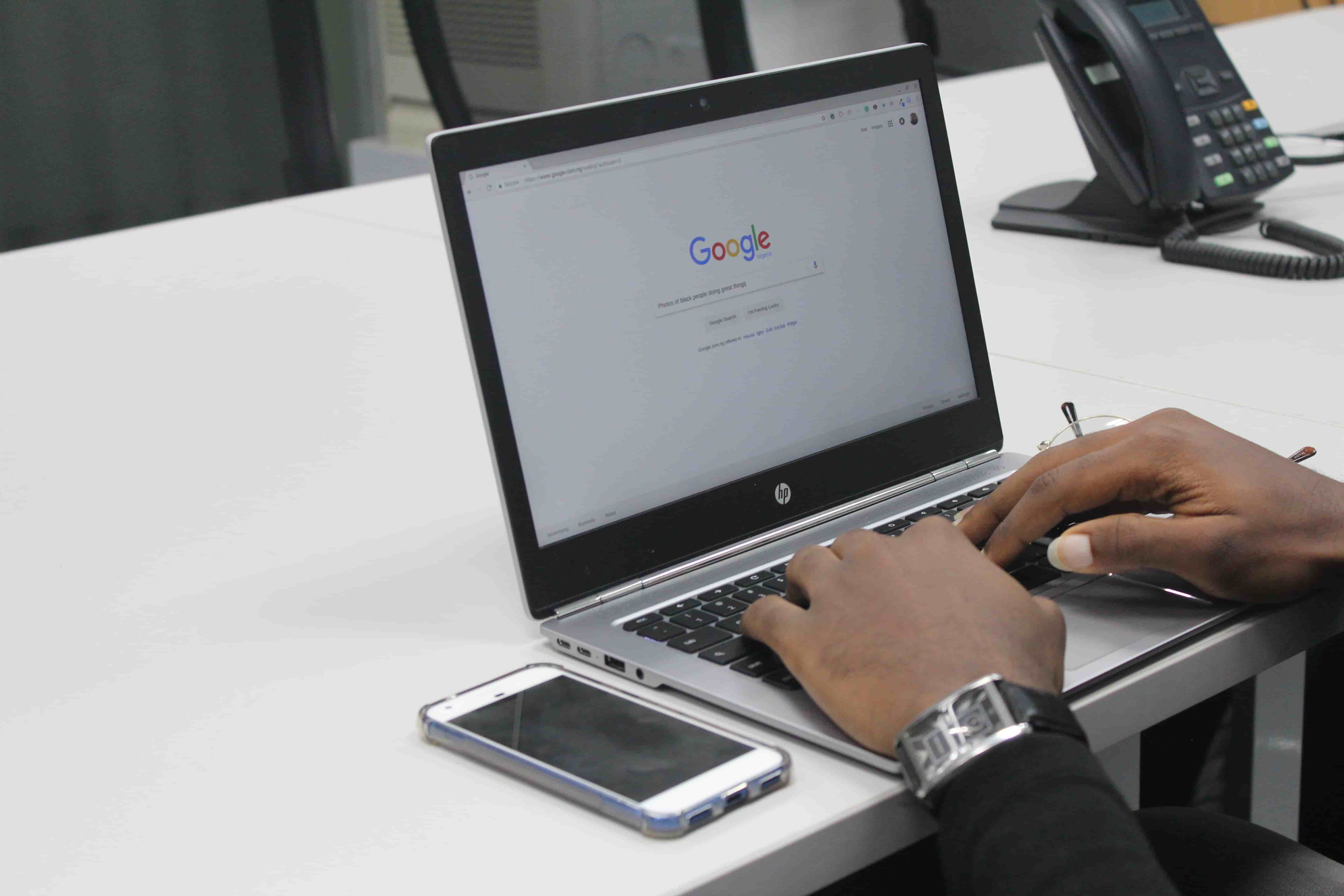 Person sitting at white office desk using HP laptop to perform a Google search