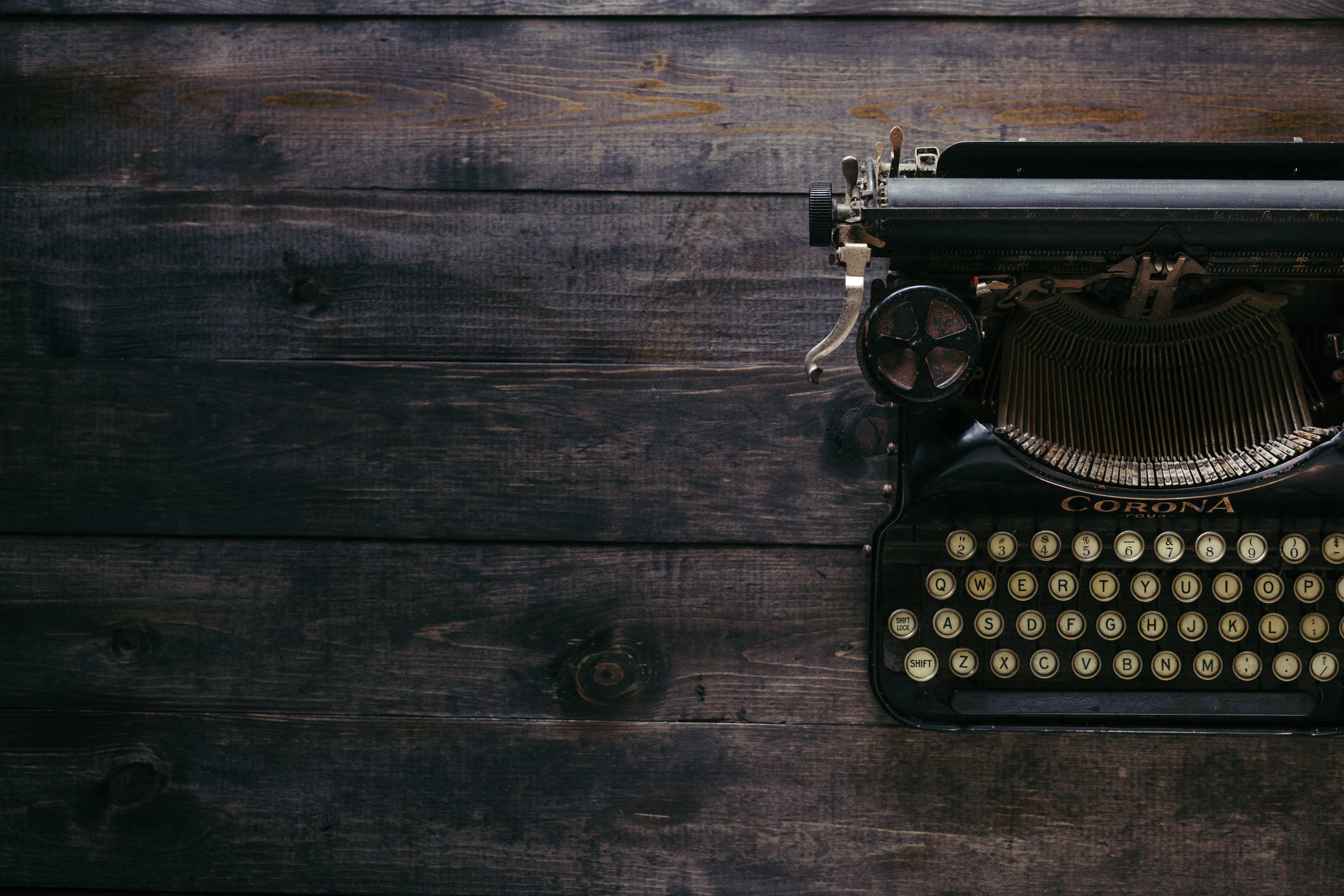 Old-fashioned typewriter on weathered brown wood table