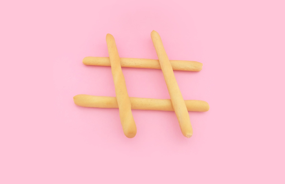 Four wooden sticks creating hash symbol on solid pink background