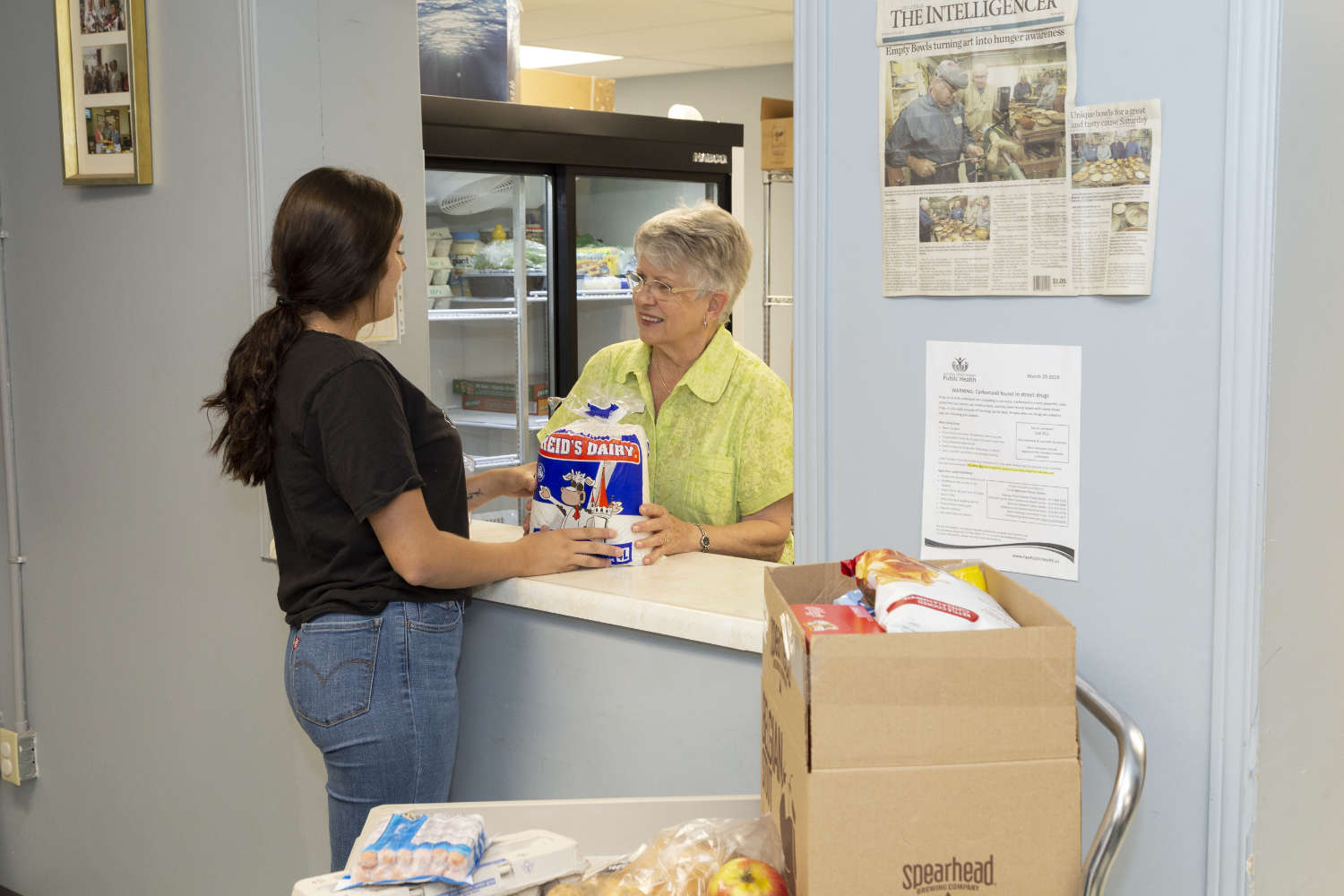 young woman receiving donated food from a volunteer at the food bank