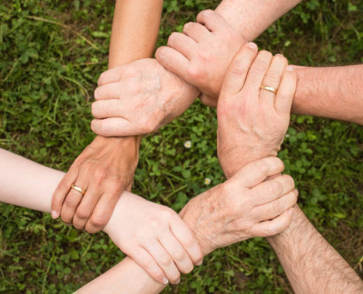 depiction of teamwork showing hands in a circle holding other people's wrists