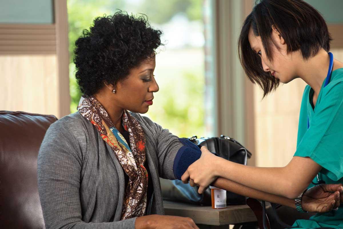 A female nurse putting a blood pressure cuff on a patient