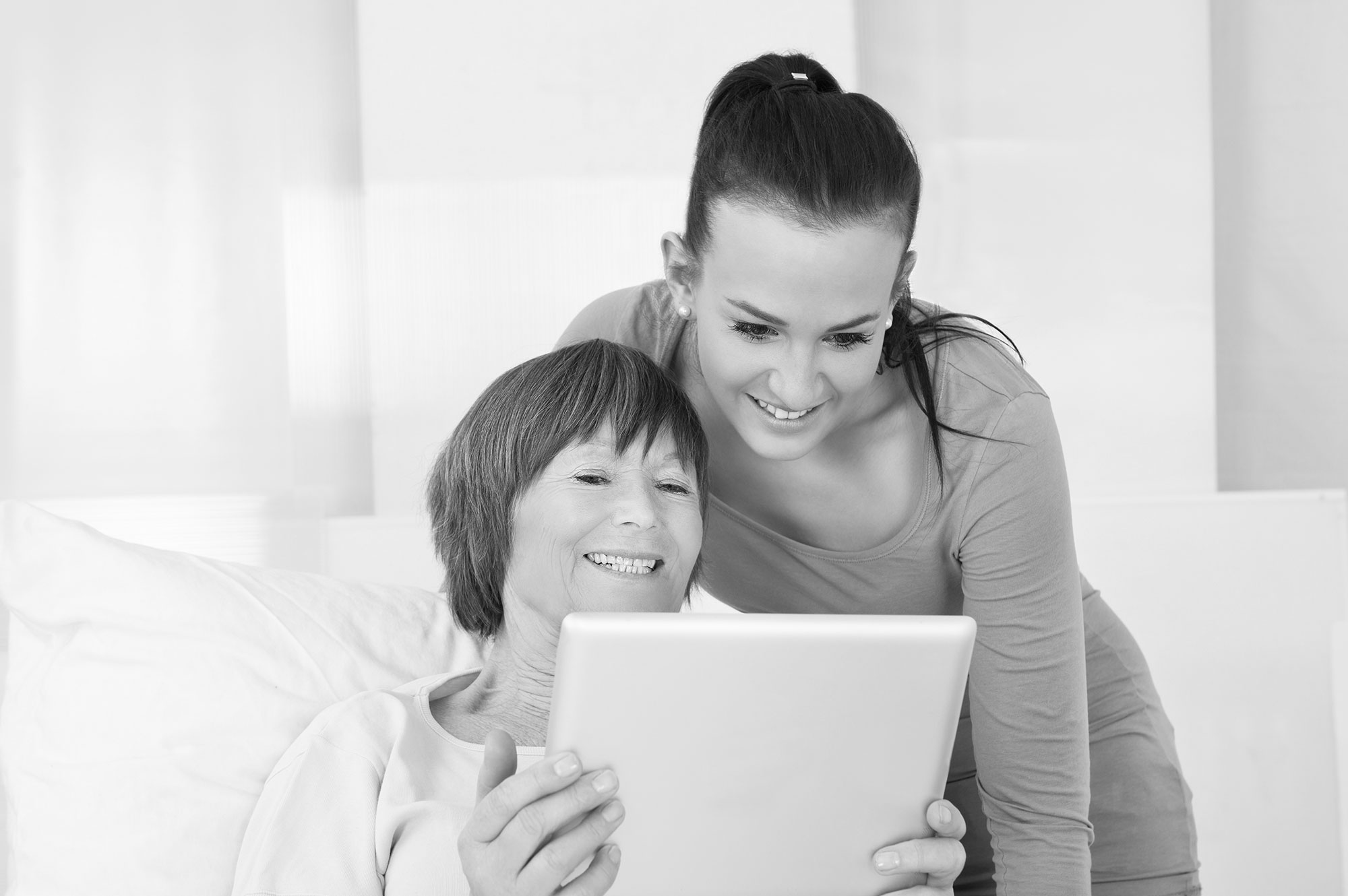 A young woman helping an older woman use a tablet
