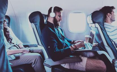 Muž na palubě letadle se sluchátky na hlavě
