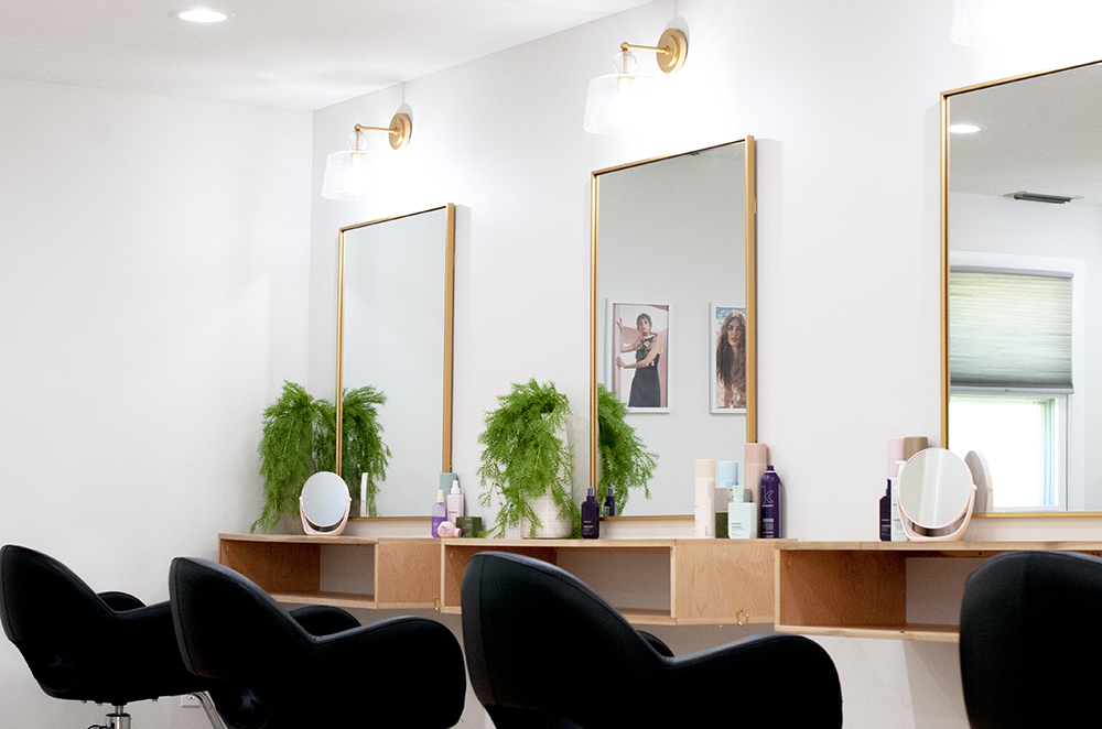 Three salon chairs against a wall of mirrors in the bright CRAFT main room.