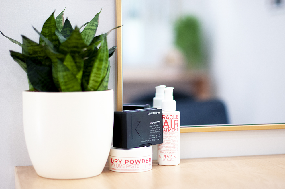 Three hair products arranged near a plant and a mirror on a shelf.