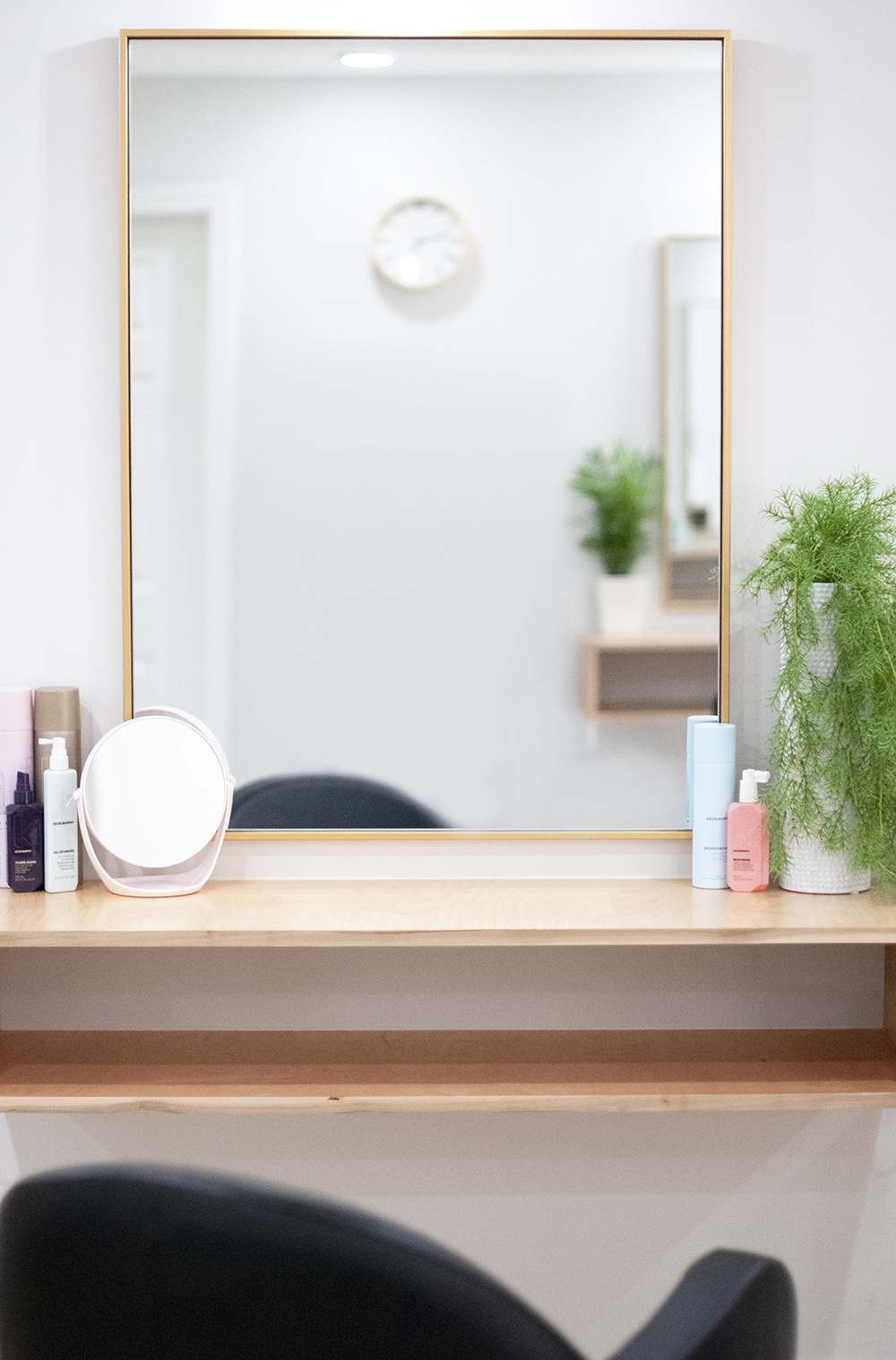 A mirror and salon products on a shelf.