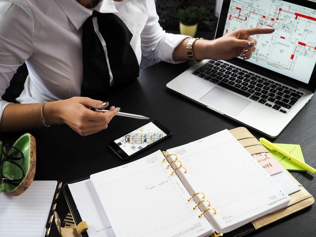 Persona mostrando planos arquitectónicos en una laptop.