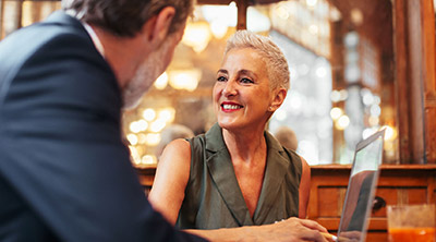 A woman discussing when she can retire with her financial advisor.
