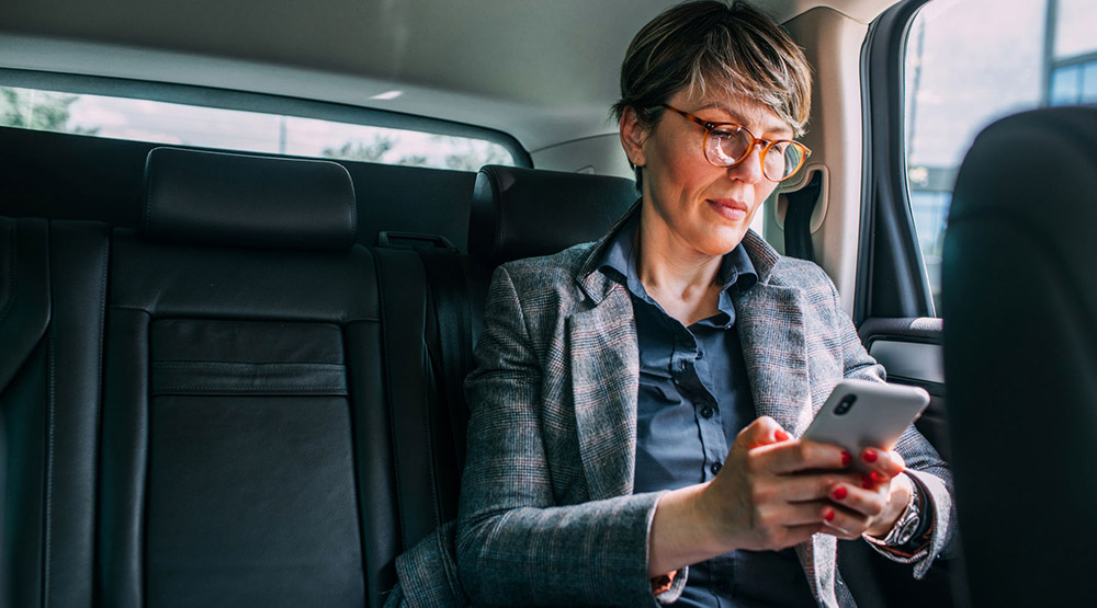 A woman riding in a car while looking over her Social Security benefits on her phone.