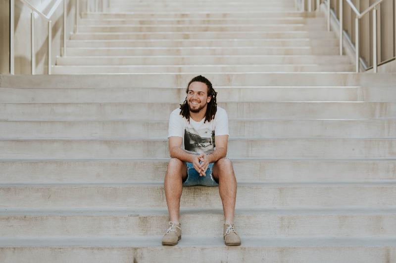 man sitting on steps smiling