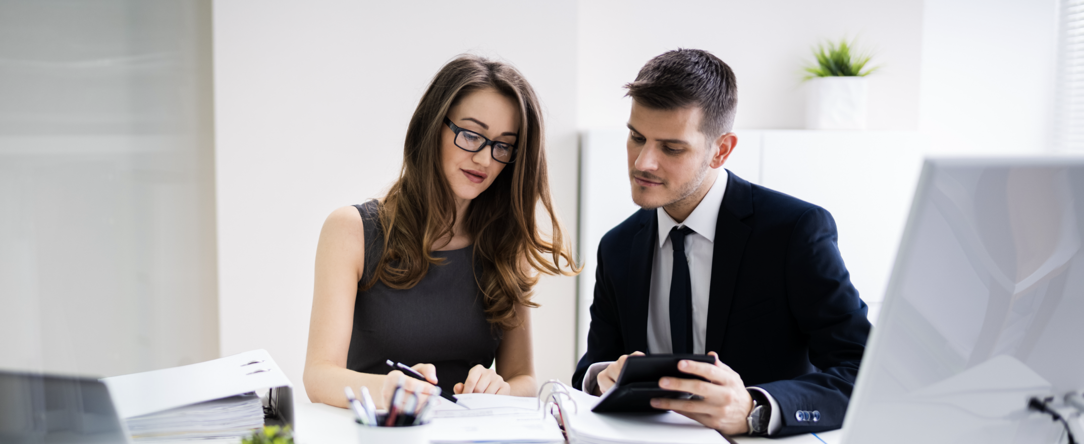 Two Young Businesspeople Calculating Invoice Calculator Stock Photo