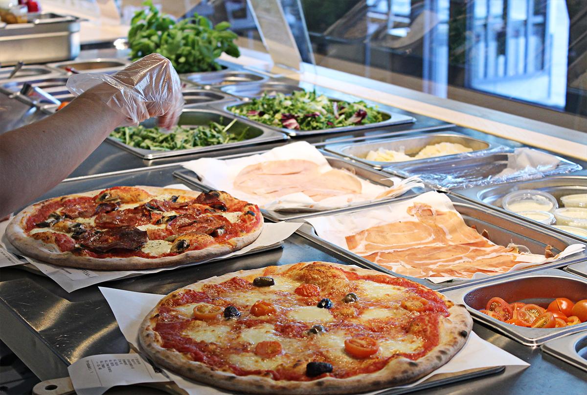 Alla tillbehör skivas på plats: parmaskinka, parmesan och grönsaker. Fredos gör pizzan från grunden, utan halvfabrikat eller konserveringsmedel.