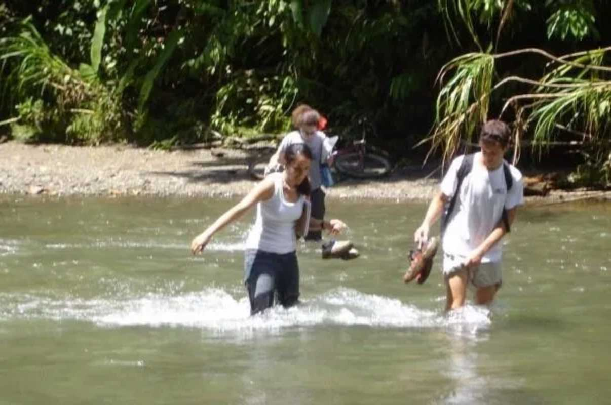 Photo of Dr. Shaina Holman on a missions trip walking through a river
