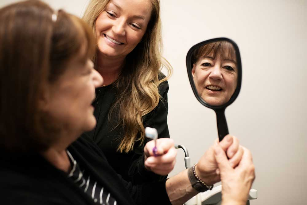 Photo of a patient looking at herself in the mirror, with a smiling team member standing beside
