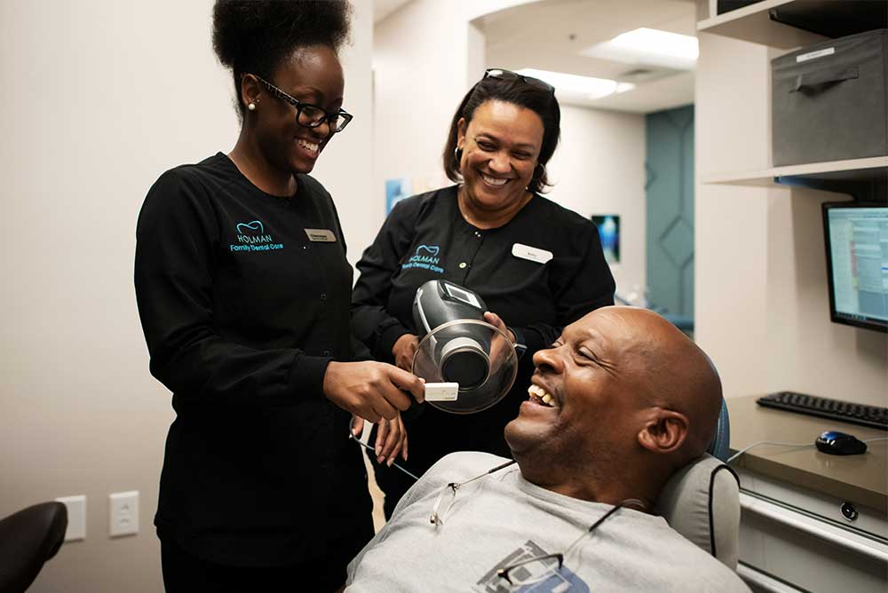 Photo of two team members and a smiling patient