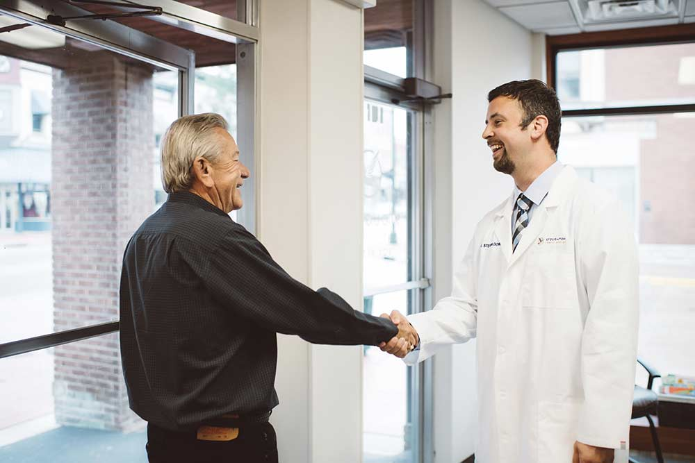 Photo of a team member shaking a patient's hand