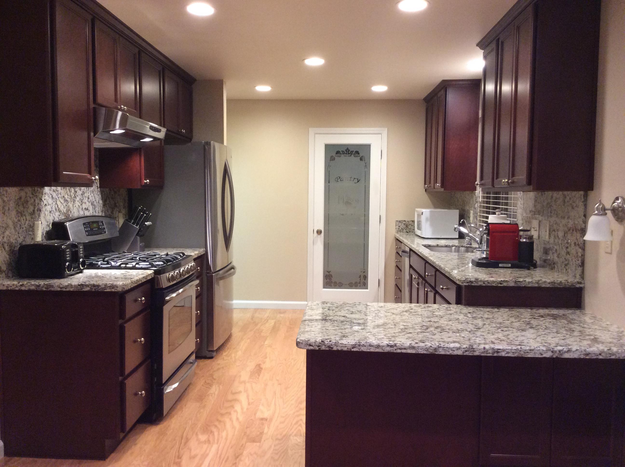 Kitchen, white granite counters and deep mahogany cabinets]
