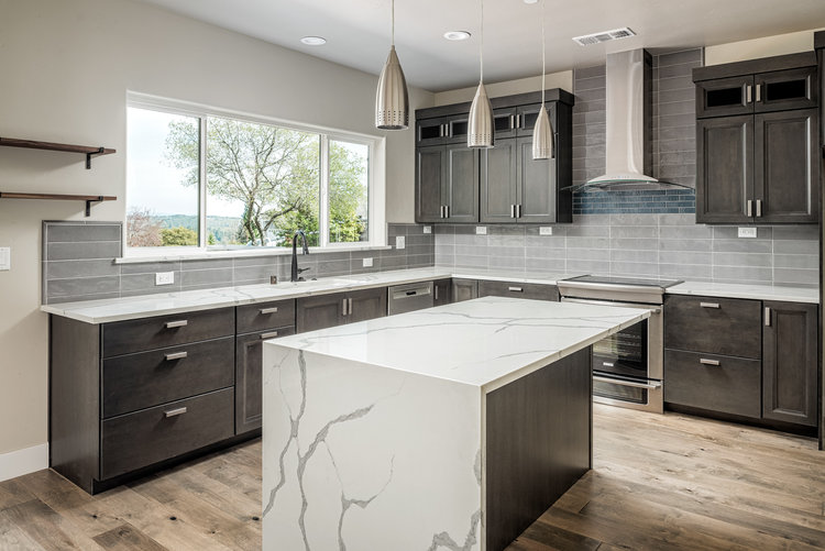 Contemporary kitchen with grey cabinets and white and grey marble countertops